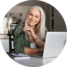 older woman next to laptop smiling