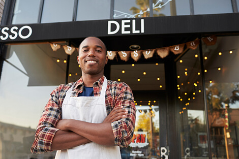 business owner standing in front of his deli