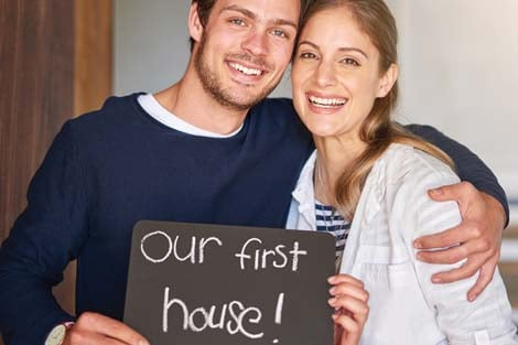 Couple holding sign that reads Our First House