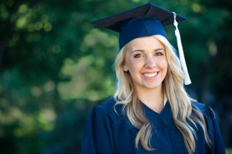 A woman smiling at the camera on graduation day