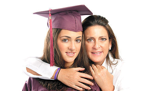 A girl in a cap and gown with her mom hugging her.