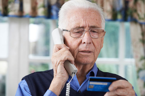 A maturely-aged man on his cellphone while holding his credit card