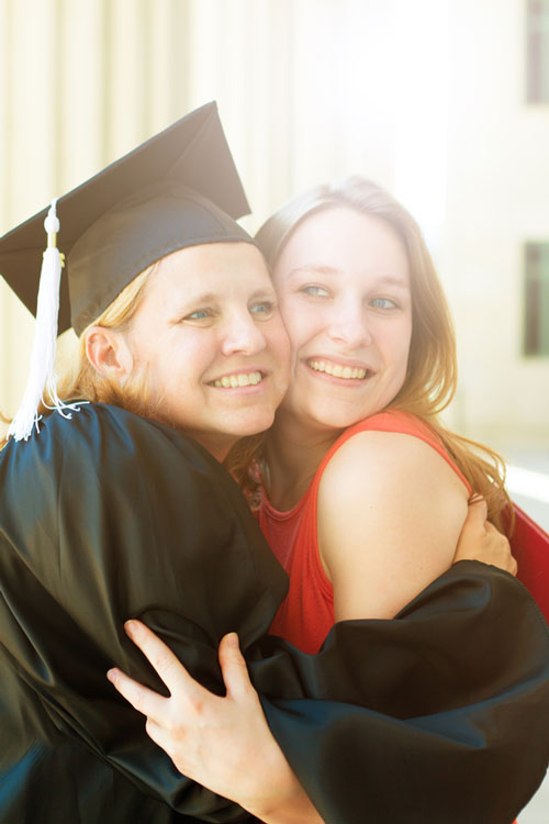 A mother and daughter hug while at the mother's graduation