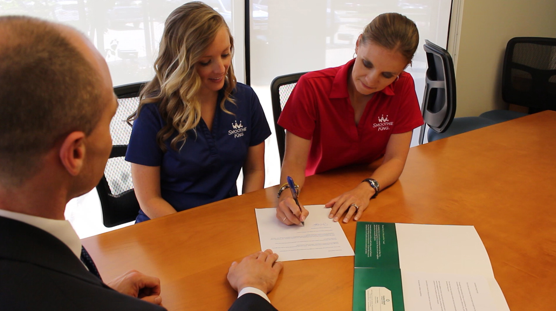Jackie and Kelli signing paperwork for their Smoothie King locations