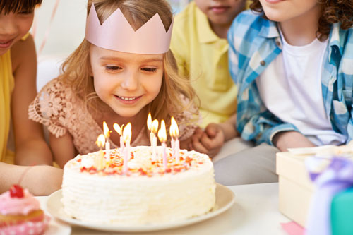 Young girl blowing out candles of her birthday cake