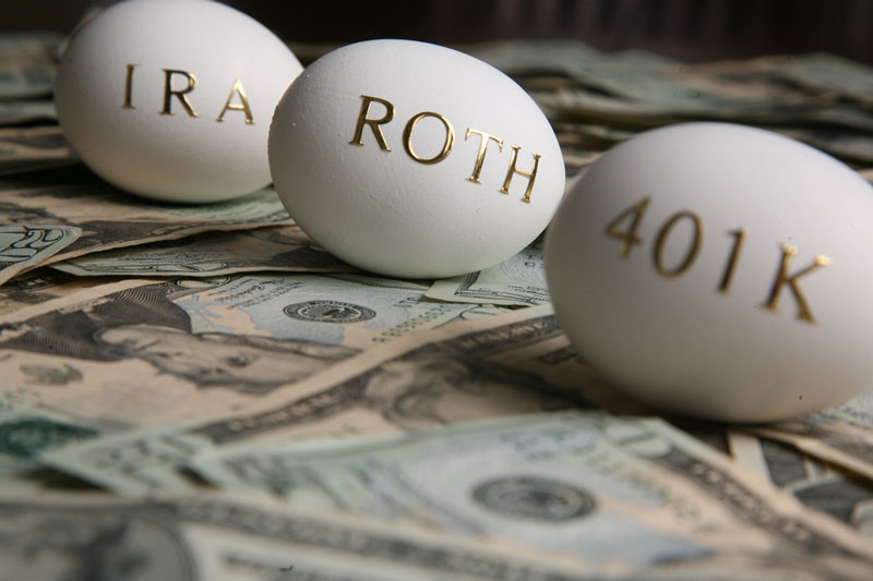 Three eggs sitting on money with the words IRS, ROTH, 401k