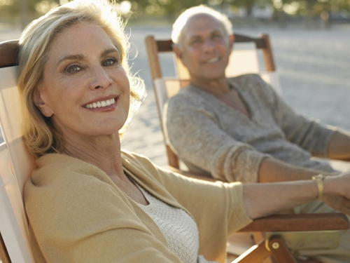 A middle-aged couple relaxing on the beach thinking about buying a new home