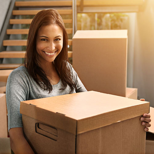 A woman holding a moving box in her new home