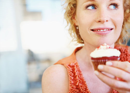 Woman looking away while holding a cupcake