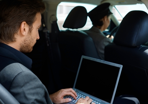 A young man works on his laptop while in the back of a taxi